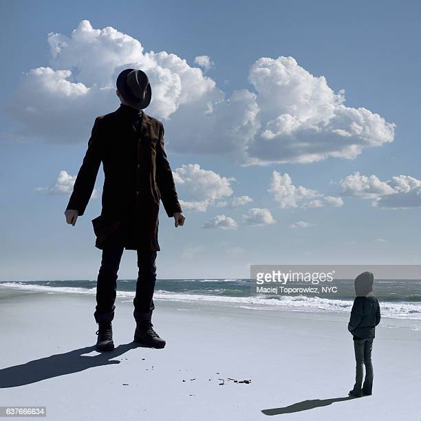 view of two people facing each other on a beach. - giants stock photos and pictures