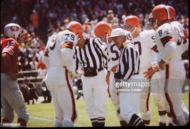 View of two unidentified referees both with cameras around their necks as they talk plays from the Cleveland Browns and the San Francisco 49ers...