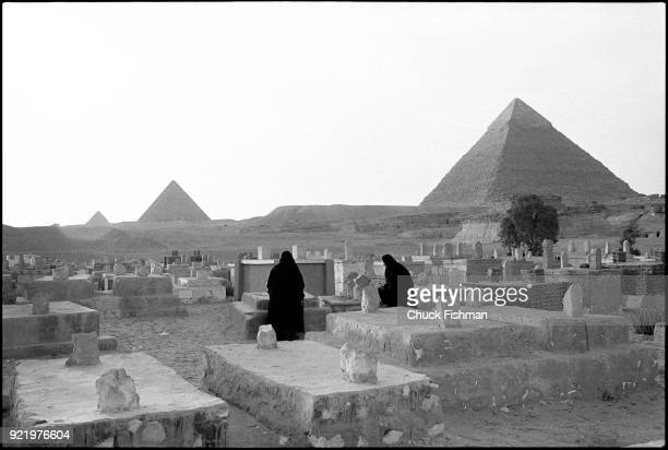 View of two unidentified women in widow's weeds as they visit graves at a cemetery in the Giza pyramid complex Egypt December 1979 The pyramids are...
