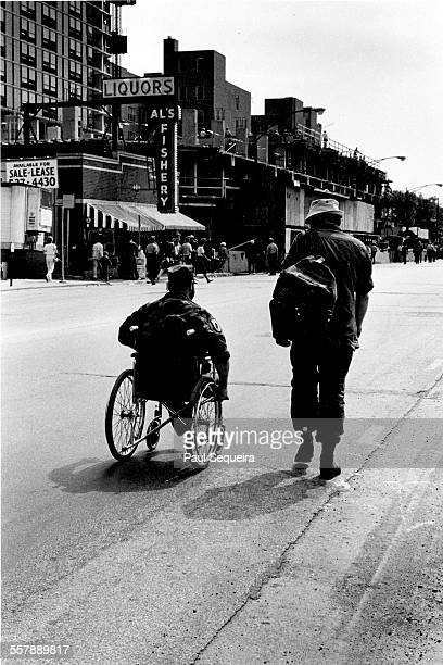 View of two Vietnam War veterans one in a wheelchair on a Grand Avenue after Vietnam Veteran's Day Parade Chicago Illinois 1979 Visible in the...