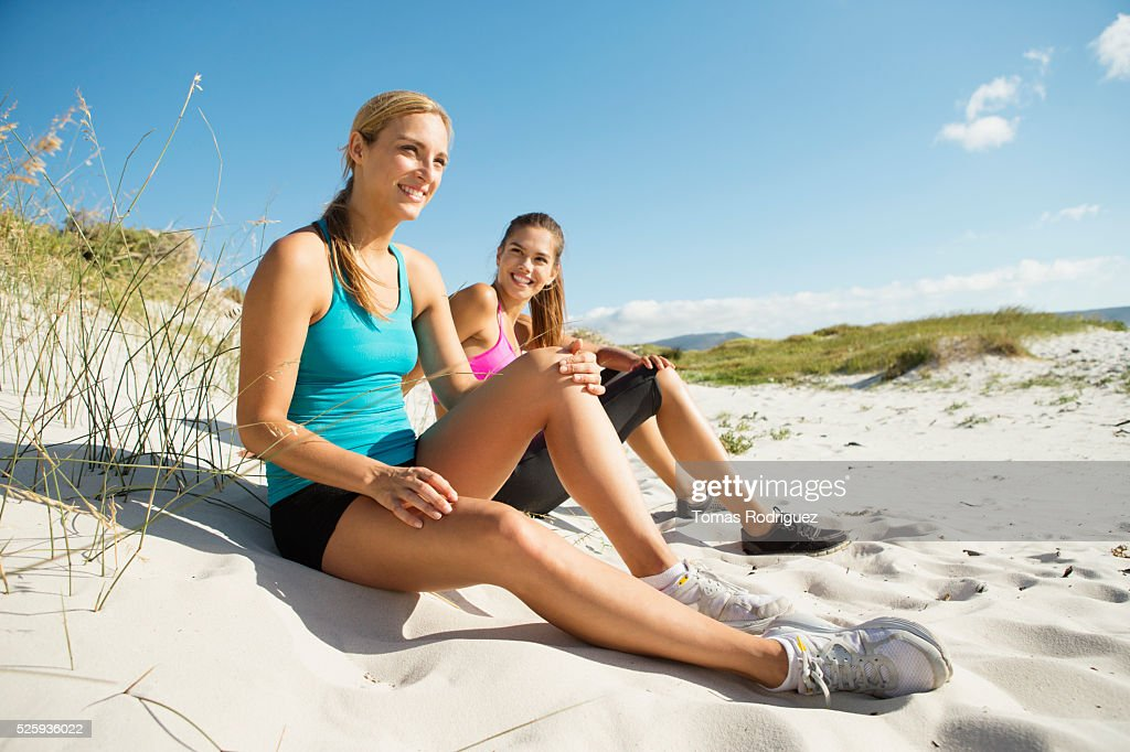 View of two young adult women sitting on dune : Stock Photo