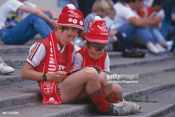 View of two young boys and Arsenal football fans dressed in Arsenal kit with matching hats and scarfs reading a programme together on a stadium...