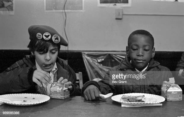 View of two young boys as they eat during a free breakfast for children program sponsored by the Black Panther Party, New York, New York, winter 1969.