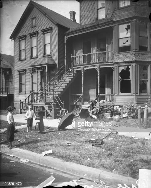 View of two young boys outside a home, with broken windows and debris in the front yard, which had been vandalized during a race riot, Chicago,...
