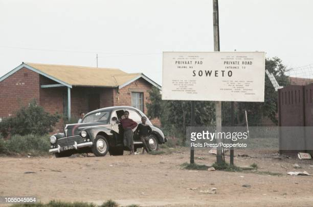 View of two young boys standing next to a parked car beside a sign next to an entrance to the township of Soweto in Johannesburg South Africa in 1970...