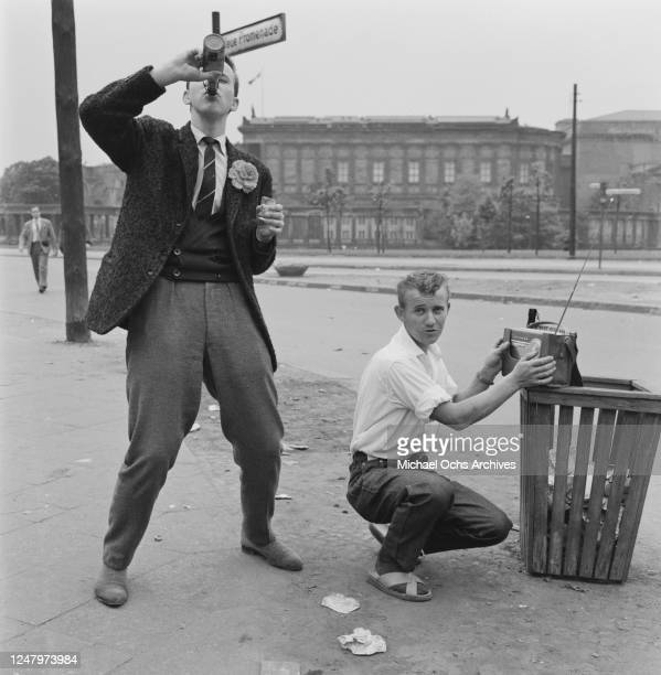 View of two young men, one drinking from a bottle and the other tuning a portable radio, on the Neue Promenade during the May Day celebrations in...