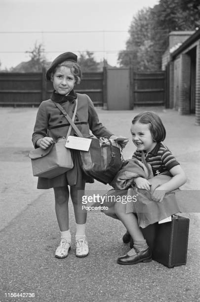 View of two young school children each carrying a suitcase gas mask satchel and a label waiting in the playground of their school as they wait for...
