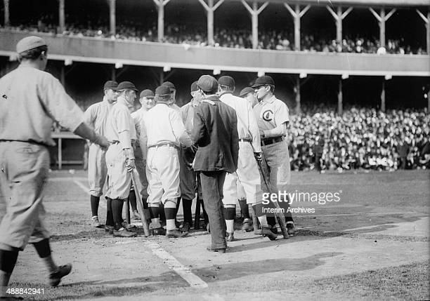 View of umpires and baseball players from the Chicago Cubs and the New York Giants gather together to discuss a call during a game at the Polo...