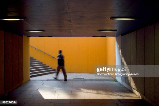 View of underpass and stairwell on London's south bank including blurred figure, UK.