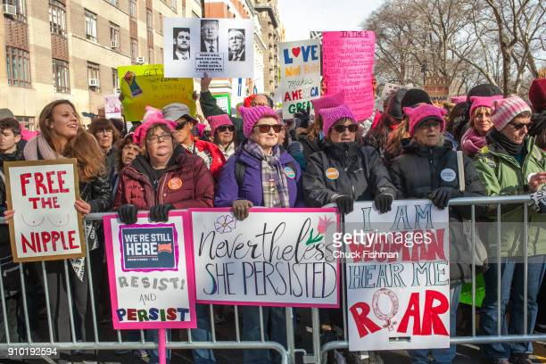 View of unidentified demonstrators many with signs as they lean against a barricade on Central Park West prior to the start of the Women's March on...