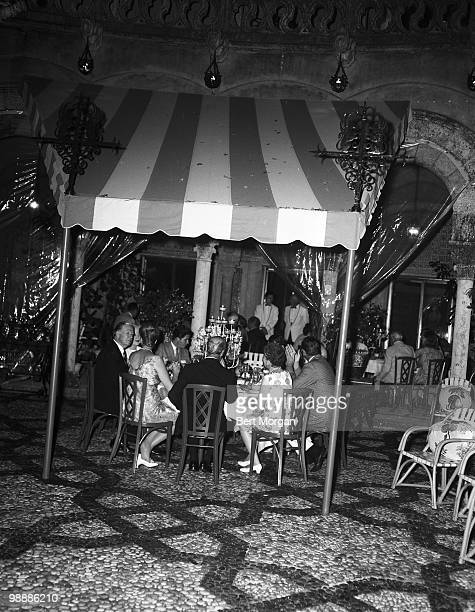 View of unidentified guests under a striped awning on the tiled garden terrace at MaraLago Palm Beach Florida mid 1950s The residence designed by...