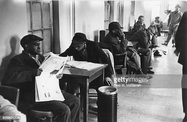 View of unidentified men as they sit at tables and read newspapers in the Municipal Lodging House New York New York February 24 1967