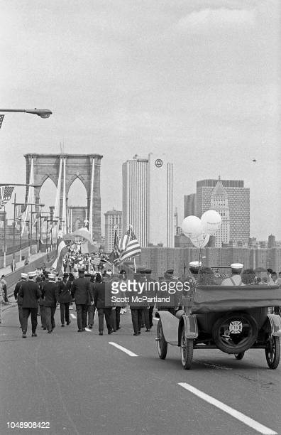 View of uniformed marchers in front of an antique car as they make their way across the Brooklyn Bridge during its 100th birthday celebrations in...