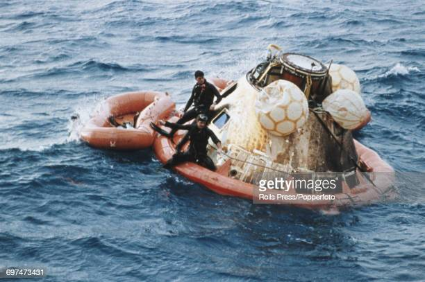 View of United States Navy frogmen from USS Yorktown standing on an inflatable surrounding the Apollo 8 Command Module capsule containing NASA...