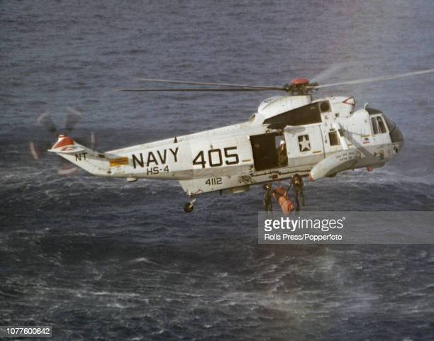 View of United States Navy helicopter from recovery ship USS Iwo Jima hovering above the Apollo 13 Command Module Odyssey as the team prepares to...