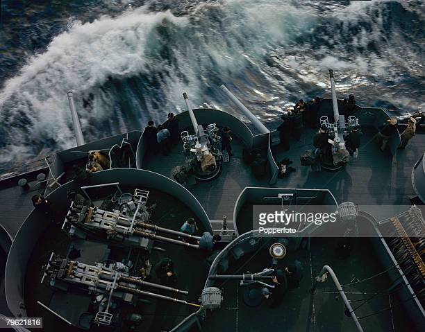 View of United States Navy personnel manning anti-aircraft guns on board the USS Arkansas dreadnought battleship on convoy escort duty in the North...