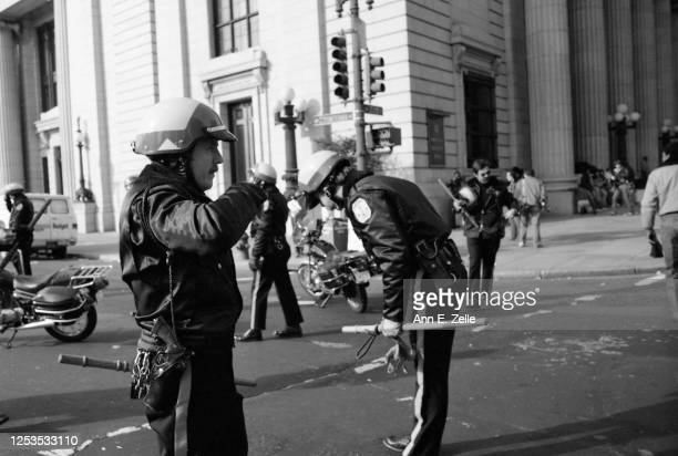 View of United States Park Police, one overcome by tear gas, on 15th Street NW during an anti-KKK protest, Washington DC, November 27, 1982. The...