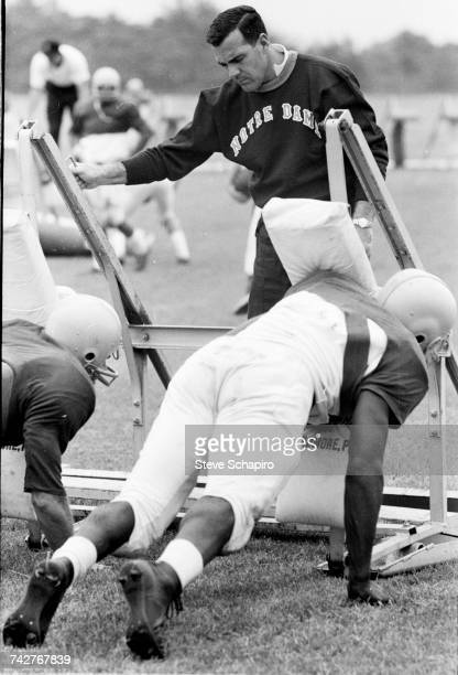 View of University of Notre Dame football coach Ara Parseghian as he oversees his players practice tackling using a football sled on the field South...