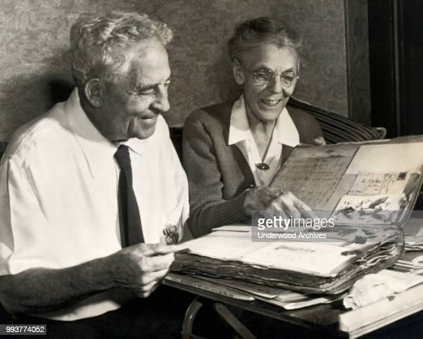 View of University of the Pacific football coach Amos Alonzo Stagg and his wife, Stella, as they look through a scrap book, Stockton, California,...