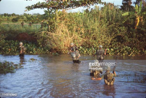 View of US Army troops from the joint Army/Navy Mobile Riverine Force wade ashore from the My Tho River during Operation Coronado Nine Mekong Delta...