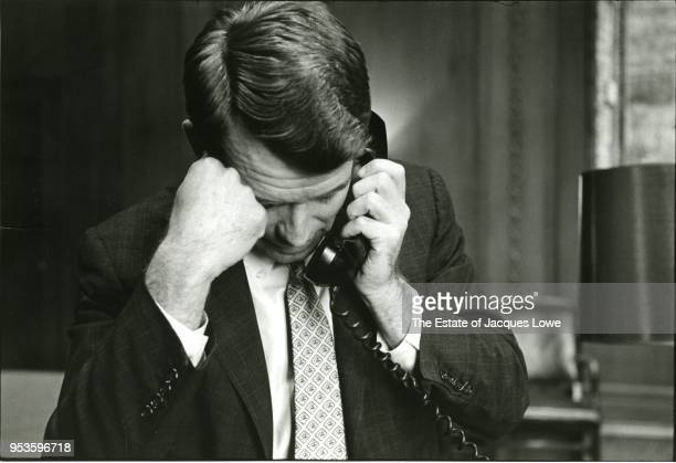View of US Attorney General Robert F Kennedy one hand on his head and a telephone in the other as he listens his head bowed down early 1960s