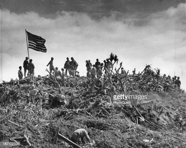 View of US Marines as they stand beside an American flag planted atop Mt Suribachi Iwo Jima Japan February 23 1945 This was the second flag raised...