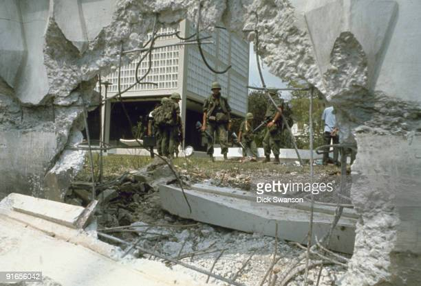 View of US soldiers through a hole in the perimeter wall in the aftermath an attack on the US Embassy during the Tet Offensive Saigon Vietnam early...