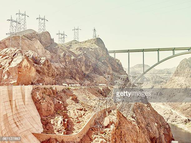 View of valley rock face with distant bridge and pylons at Hoover Dam, Nevada, USA