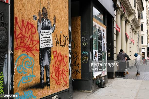 View of vandalized street art of Dr. Martin Luther King, Jr. On a boarded-up storefront in the SoHo neighborhood of Manhattan on January 17, 2021 in...