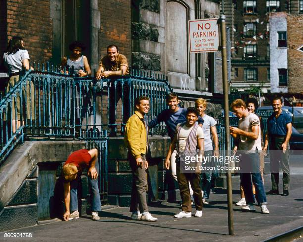 View of various cast members among them American actor Russ Tamblyn on a sidewalk in a scene from 'West Side Story' 1961