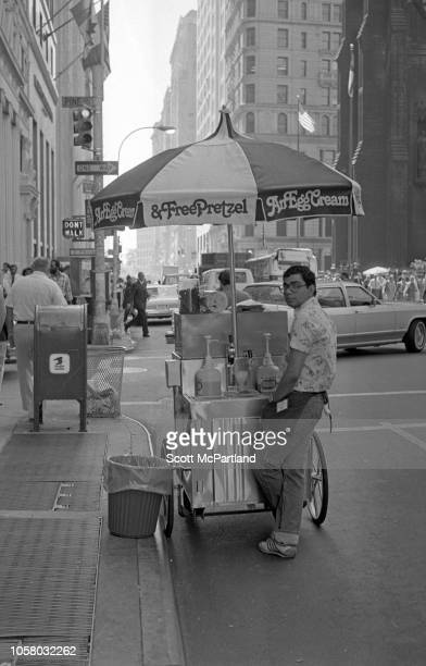 View of vendor as he stands next to his egg cream cart on Broadway in lower Manhattan New York New York September 1980 Partly visible at extreme...