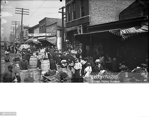 View of vendors and shoppers on Jefferson Street in the Maxwell Street Market area Chicago Illinois circa 1905 Sign in Yiddish reads Fish Market