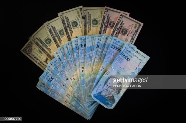 View of Venezuelan bolivar banknotes and US dollar bills in Caracas on August 2, 2018. - Venezuela's government on Thursday loosened the tight...