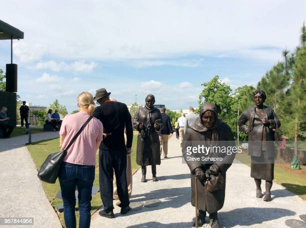 View of visitors at a sculpture commemorating the slave trade at the entrance of the National Memorial For Peace And Justice in Montgomery, Alabama,...