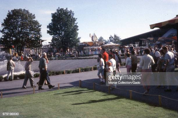 View of visitors walking next to the edge of the International Fountain at the Century 21 Expo Seattle World's Fair in Seattle Washington July 1962...