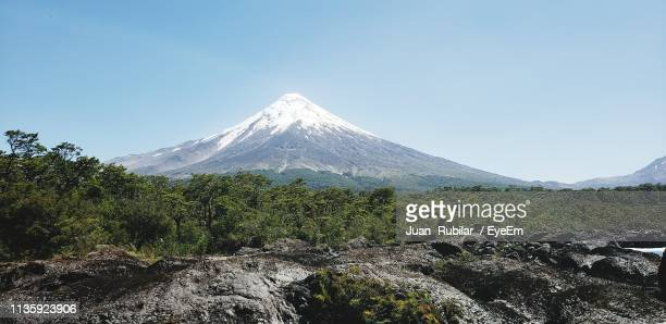 view of volcanic landscape against clear sky - petrohue river stock photos and pictures