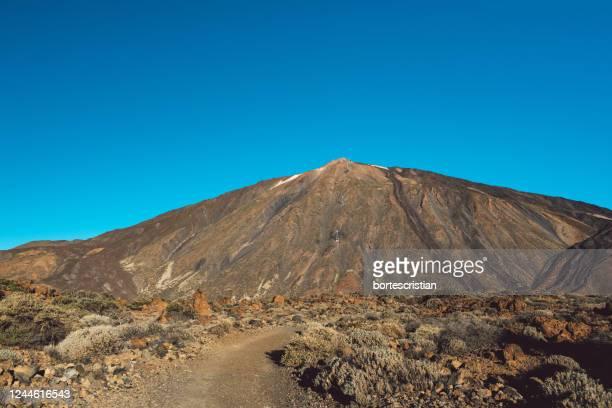 view of volcanic mountain against blue sky - bortes imagens e fotografias de stock
