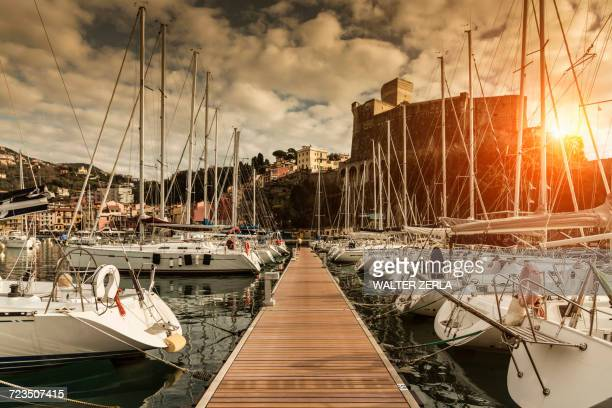 View of waterfront yachts and castle at sunset, Lerici, Liguria, Italy