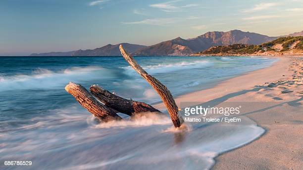 view of waves in sea against mountain range - corsica stock photos and pictures