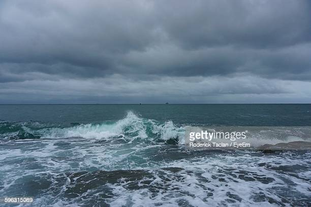 View Of Waves On Coast Against Cloudy Sky