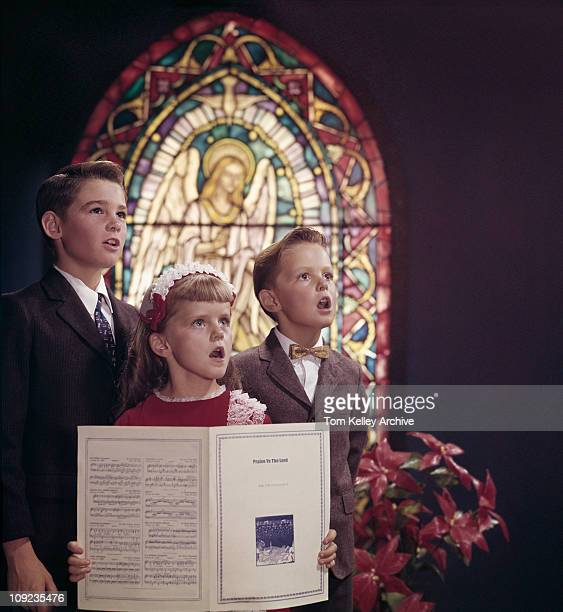 View of welldressed children two boys and a girl singing in a church choir with a stained glass window in the background 1956 The girl is holding the...