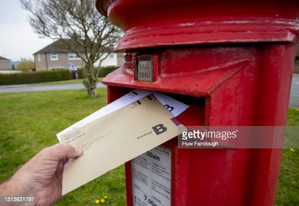 View of Welsh Government and Town Council Election postal votes being posted at a post box on April 21, 2021 in Blackwood, Wales. Welsh voters go to...
