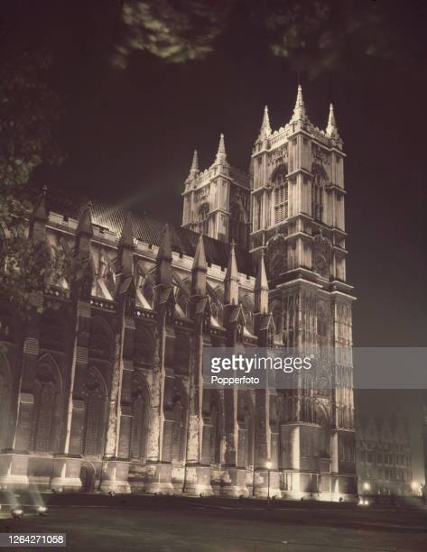View of Westminster Abbey church, lit at night by floodlight, in Westminster, London in October 1952.