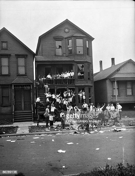 View of white children celebrating after having raided the home of African Americans during the race riots, Chicago, 1919. Note the broken windows...