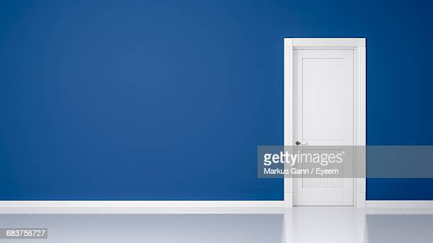view of white door on blue wall - deur stockfoto's en -beelden