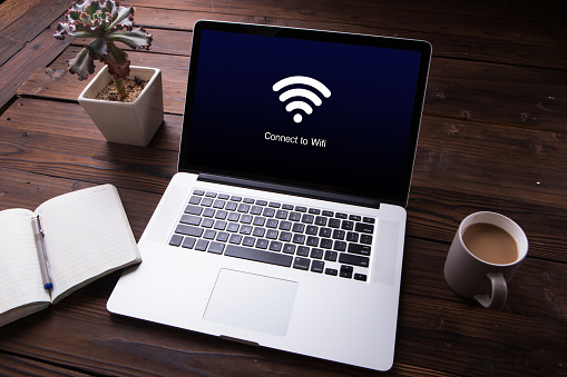View of wi-fi connection on the laptop / computer screen with office equipment on wooden desk background 1012716838