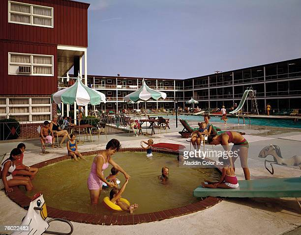 View of woman and children playing near and in the kiddie swimming pool at the Stowaway Motel Ocean City Maryland 1960s The fullsize pool is just...