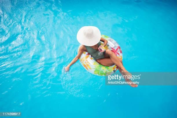 vue de femme se trouvant sur le radeau gonflable dans la piscine - flotter sur l'eau photos et images de collection