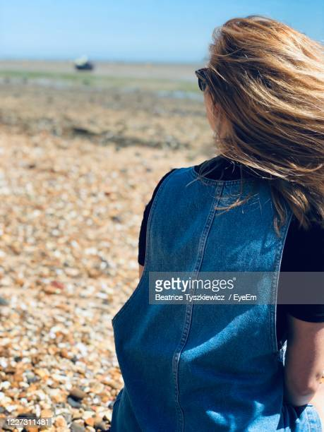 view of woman sitting on a beach - beatrice stock pictures, royalty-free photos & images