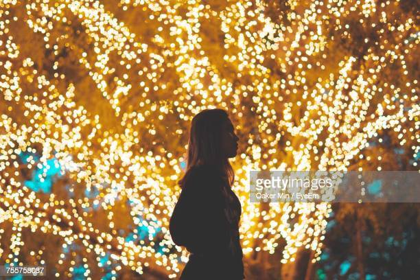 View Of Woman Standing By Illuminated Tree